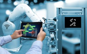 Man hand holding tablet with performance check screen software and blue tone of automate wireless Robot arm in smart factory background